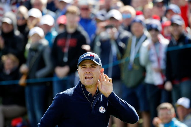 Justin Thomas cups his ear to the crowd during his fourball match on the second day of the 2018 Ryder Cup at Le Golf National.
