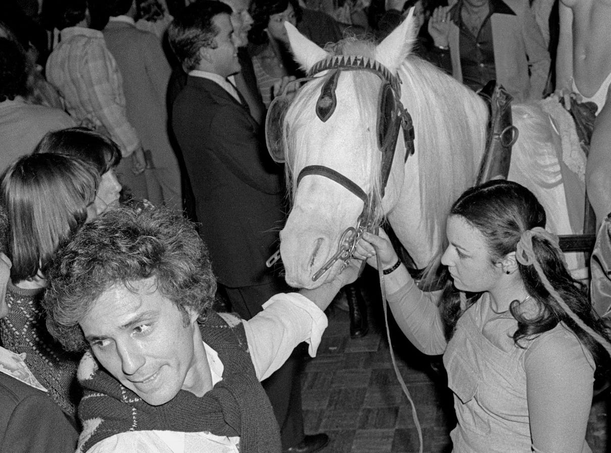 Co-founder Ian Schrager leads a woman on a white horse across the dance floor.