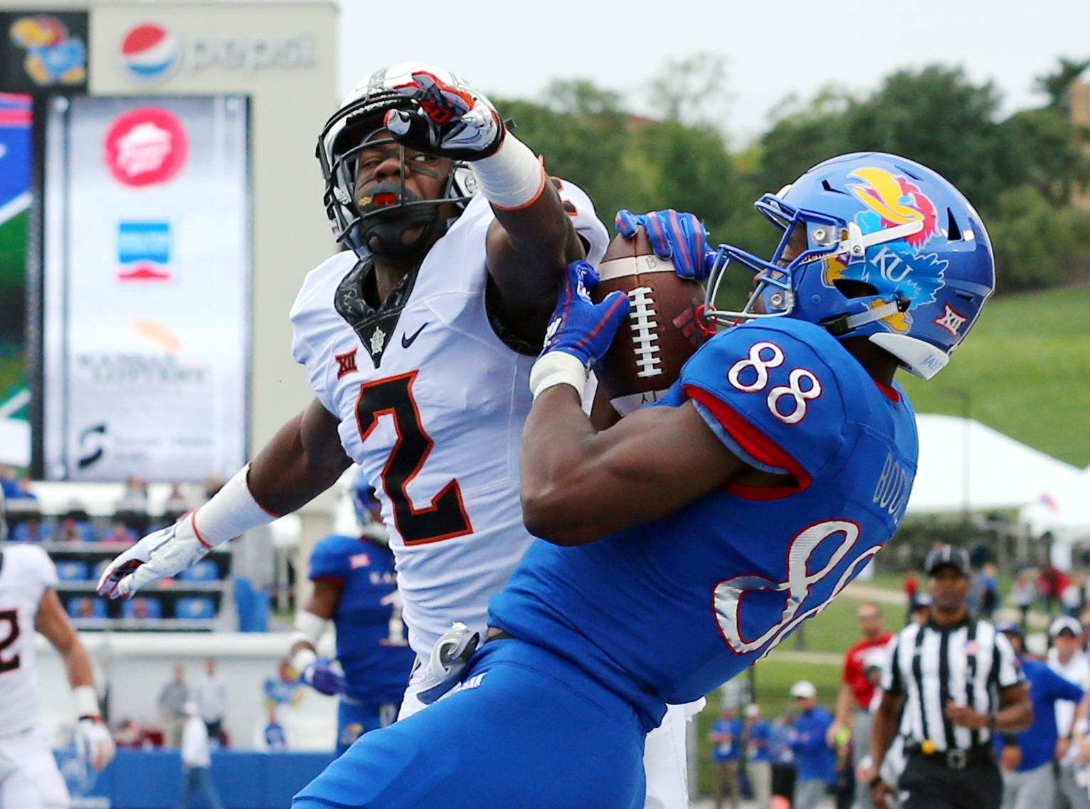 Kansas Jayhawks wide receiver Jeremiah Booker (88) catches a touchdown pass as Oklahoma State Cowboys cornerback Tanner McCalister (2) defends in the second half at Memorial Stadium.