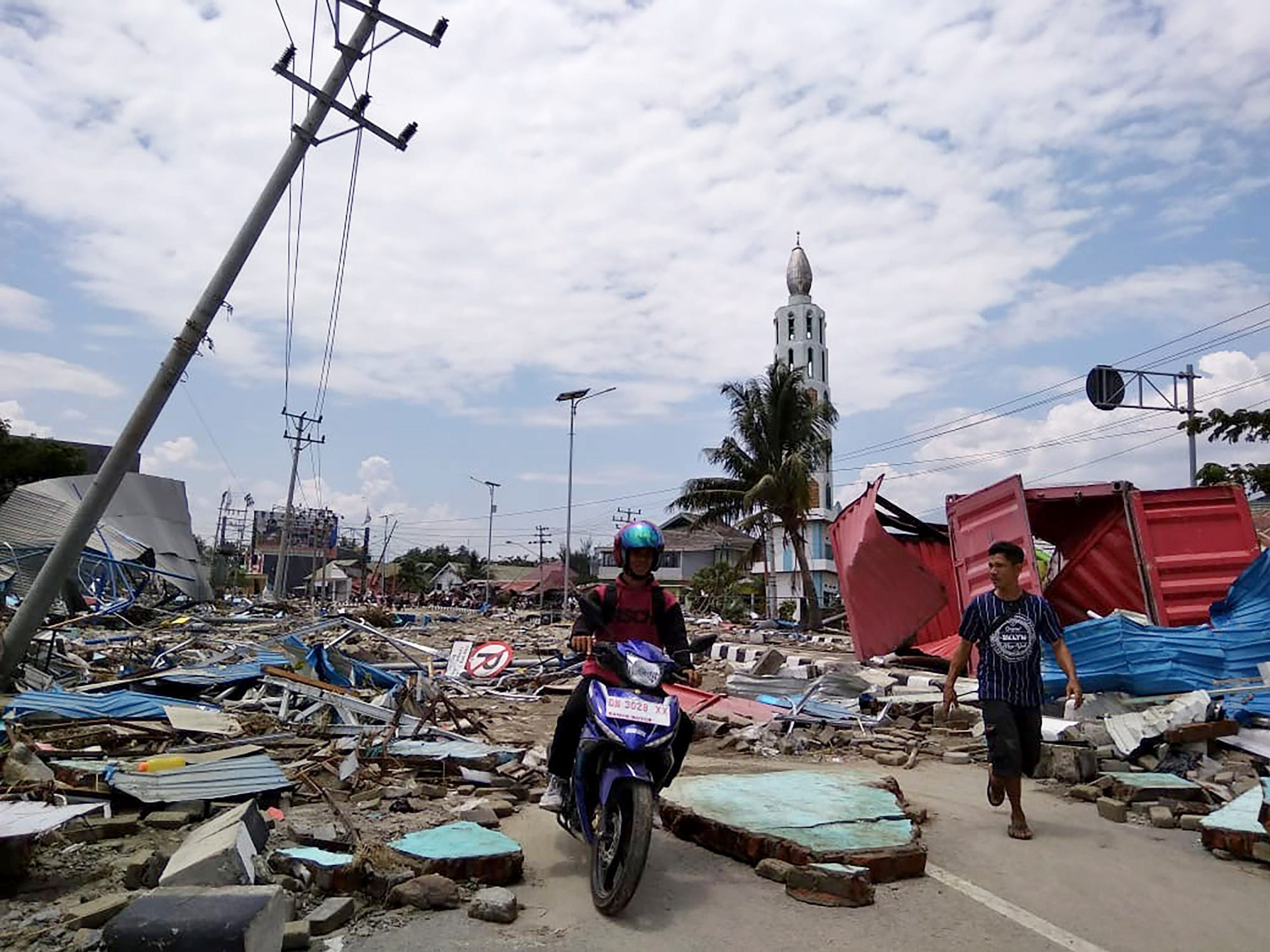 Residents make their way along a street full of debris after an earthquake and tsunami hit Palu, on Sulawesi island on Saturday.