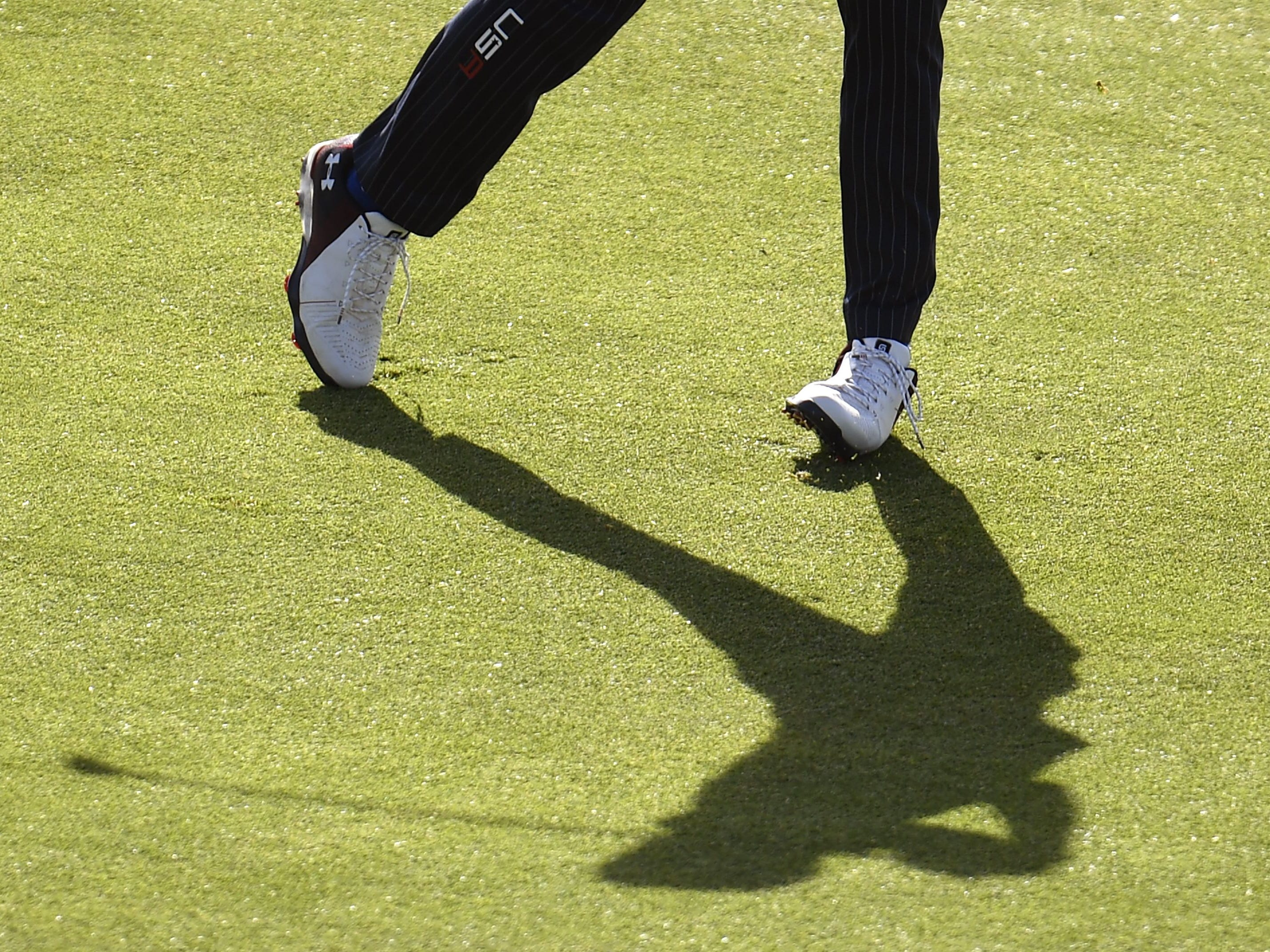 Jordan Spieth's shadow tags along on an approach shot during Saturday's fourball matches.