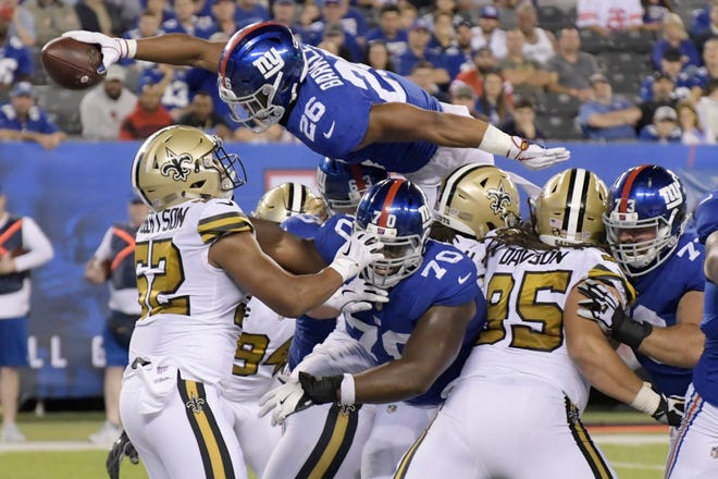 New York Giants' Saquon Barkley jumps over defenders for a touchdown during the second half of an NFL football game against the New Orleans Saints.