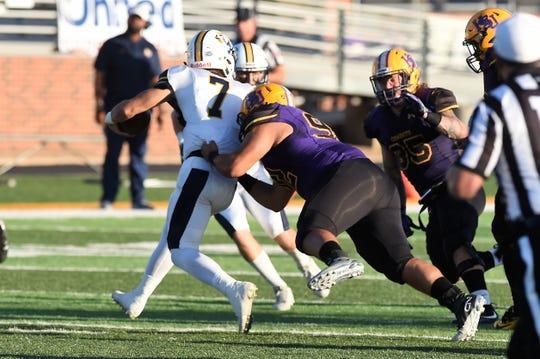 Hardin-Simmons defensive lineman Zack Cedillo (92) grabs East Texas Baptist quarterback Brian Baca (7) on Saturday, Sept. 29, 2018. The Cowboys won 59-17.