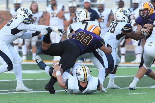 Hardin-Simmons defensive lineman Kyle Zavala (98) brings down East Texas Baptist quarterback Brian Baca (7) on Saturday, Sept. 29, 2018.