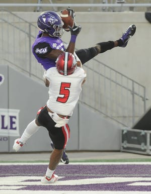 ACU's Torin Justice hauls in a 4-yard touchdown pass from Luke Anthony as Incarnate  Word's Dalvin Fillmore (5) defends. The TD gave ACU a 28-20 lead 1:59 before halftime of the Southland  Conference  game Saturday, Sept. 29, 2018, at Wildcat Stadium.