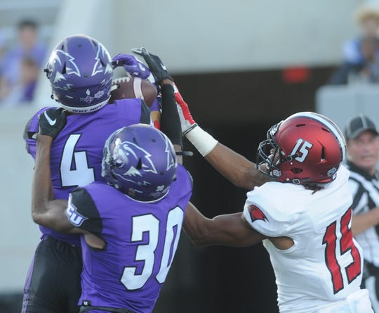 ACU's Erik Huhn (4) picks off a Jon Copeland pass in the end zone as  Obinna Udoye (30) and Incarnate Word's Jaelin Campbell look on 13:28 before halftime.  The Wildcats cashed the pick into a 1-yard TD run by Tracy James, giving ACU a 21-14 lead during the Southland Conference game Saturday, Sept. 29, 2018, at Wildcat Stadium.