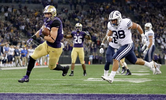 Washington tight end Drew Sample (left) runs for a second-half touchdown after hauling in a pass from Jake Browning.