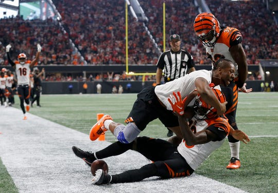 Injured running back Joe Mixon tackles wide receiver A.J. Green (18) after he catches the game-winning touchdown in the fourth quarter of the NFL Week 5 game between the Atlanta Falcons and the Cincinnati Bengals at Mercedes-Benz Stadium in Atlanta on Sunday, Sept. 30, 2018. The Bengals scored a touchdown in the final seconds of the fourth quarter to win 37-36.