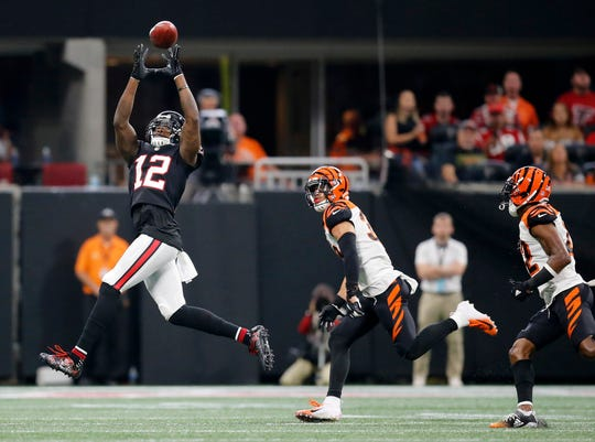 Atlanta Falcons wide receiver Mohamed Sanu (12) stretches for a first down reception in the second quarter of the NFL Week 5 game between the Atlanta Falcons and the Cincinnati Bengals at Mercedes-Benz Stadium in Atlanta on Sunday, Sept. 30, 2018.