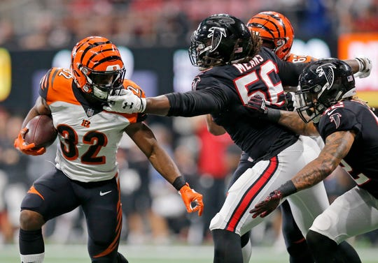 Cincinnati Bengals running back Mark Walton (32) is grabbed by Atlanta Falcons defensive end Steven Means (56) on a carry in the fourth quarter of the NFL Week 5 game between the Atlanta Falcons and the Cincinnati Bengals at Mercedes-Benz Stadium in Atlanta on Sunday, Sept. 30, 2018. The Bengals scored a touchdown in the final seconds of the fourth quarter to win 37-36.