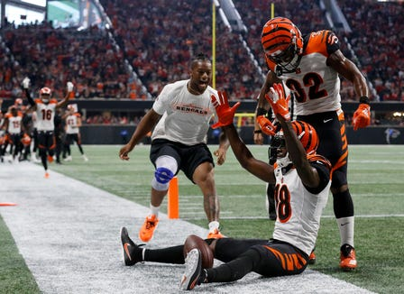 Cincinnati Bengals wide receiver A.J. Green (18) celebrates on the ground with injured running back Joe Mixon and running back Mark Walton (32) after catching the game-winning touchdown pass in the fourth quarter of the NFL Week 5 game between the Atlanta Falcons and the Cincinnati Bengals at Mercedes-Benz Stadium in Atlanta on Sunday, Sept. 30, 2018. The Bengals scored a touchdown in the final seconds of the fourth quarter to win 37-36.