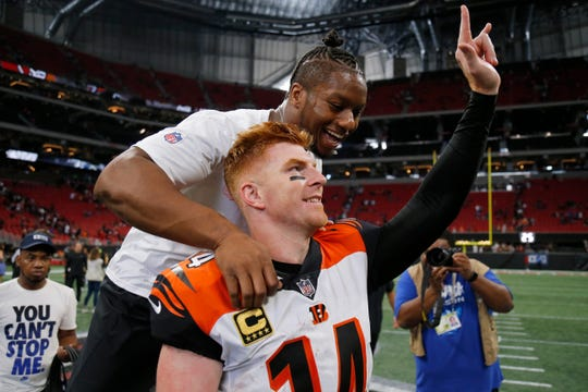 Injured running back Joe Mixon jumps on the back of quarterback Andy Dalton (14) while he waves to his family as they leave the field after the fourth quarter of the NFL Week 5 game between the Atlanta Falcons and the Cincinnati Bengals at Mercedes-Benz Stadium in Atlanta on Sunday, Sept. 30, 2018. The Bengals scored a touchdown in the final seconds of the fourth quarter to win 37-36.