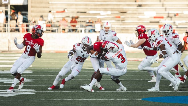Jacksonville State quarterback Chappelle Wade is tackled by Austin Peay's Keawvius Cummings (3) and Juantarius Bryant (26) on Sept. 29, 2018.