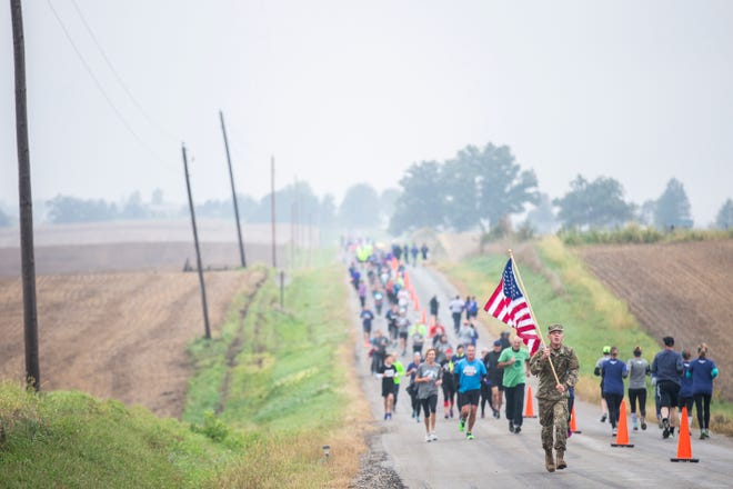 A runner carries an American flag during a memorial run for Mollie Tibbetts on Sunday, Sept. 30, 2018, in Brooklyn.