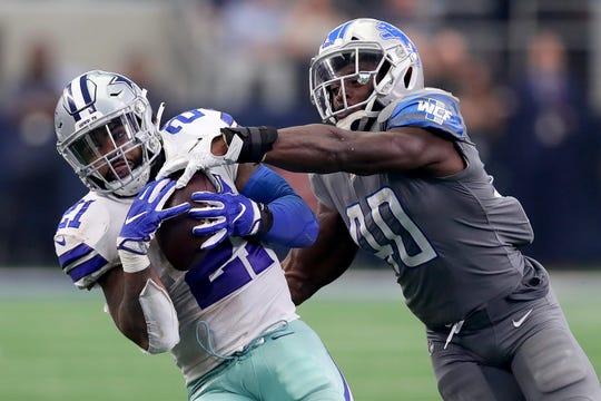 Dallas Cowboys running back Ezekiel Elliott catches a pass against Detroit Lions linebacker Jarrad Davis in the fourth quarter at AT&T Stadium on Sept. 30, 2018 in Arlington, Texas.