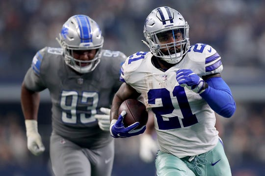 Cowboys running back Ezekiel Elliott carries the ball to score a touchdown against Lions defensive lineman Da'Shawn Hand in the second quarter in Arlington, Texas, Sunday, Sept. 30, 2018.