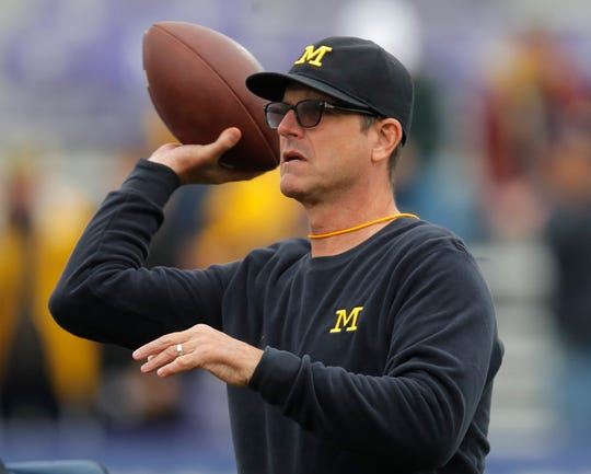 Michigan's Jim Harbaugh throws a football before the game against Northwestern Saturday, Sept. 29, 2018, in Evanston, Ill.