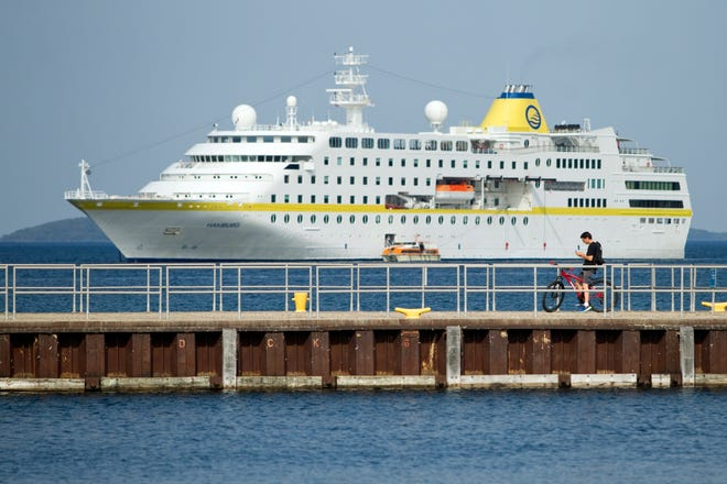 In this Tuesday, Sept. 25, 2018, photo, Jeff Clifton of Traverse City checks out the cruise ship MS Hamburg at anchor in West Grand Traverse Bay during a stop in Traverse City, Mich., on its Great Lakes cruise. The 472-foot vessel can carry around 400 passengers and 197 crew members, and is operated by the German cruise line Plantours Kreuzfahrten.