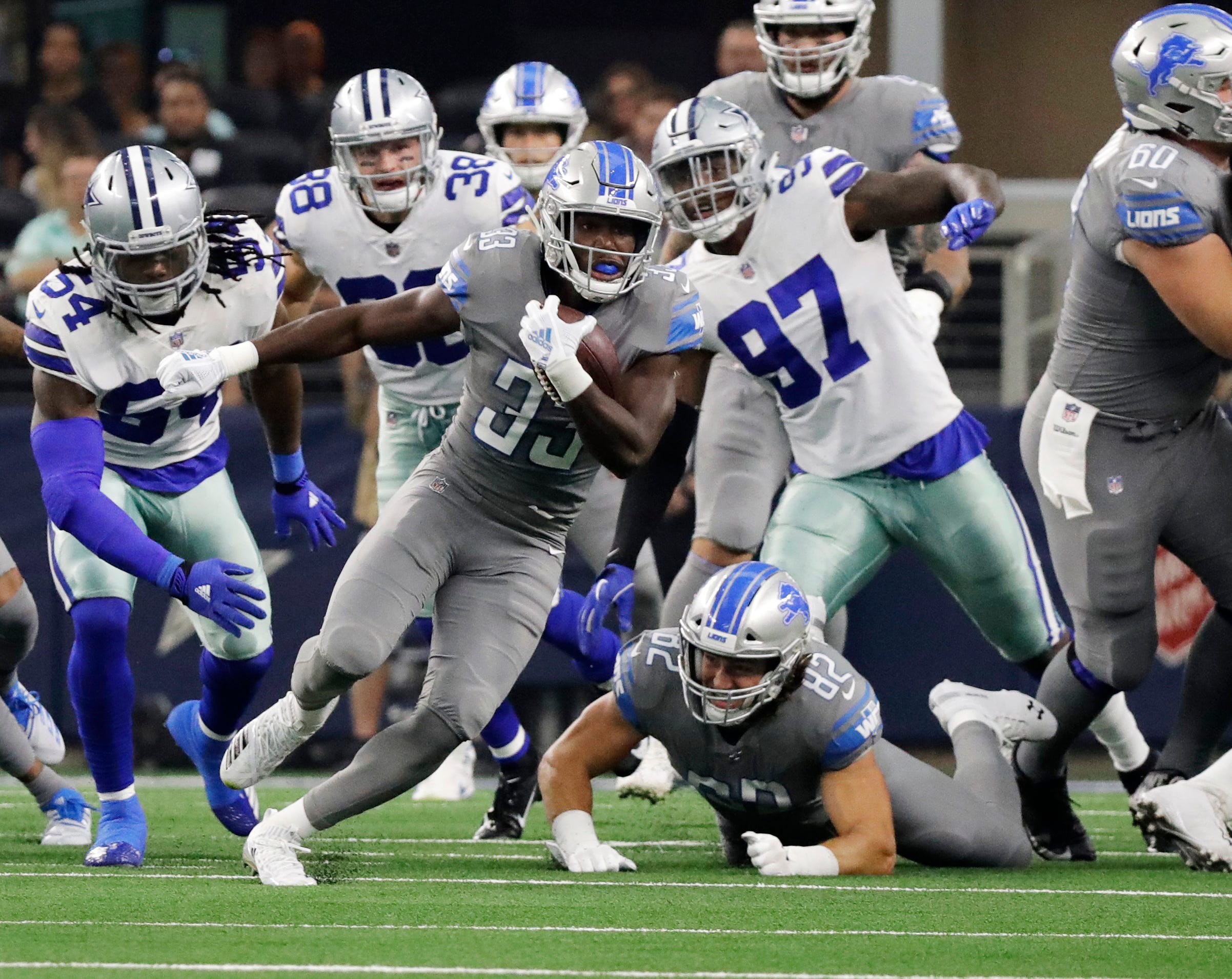 Lions running back Kerryon Johnson runs past Cowboys defensive end Taco Charlton in the first half of their game in Arlington, Texas, Sunday, Sept. 30, 2018.