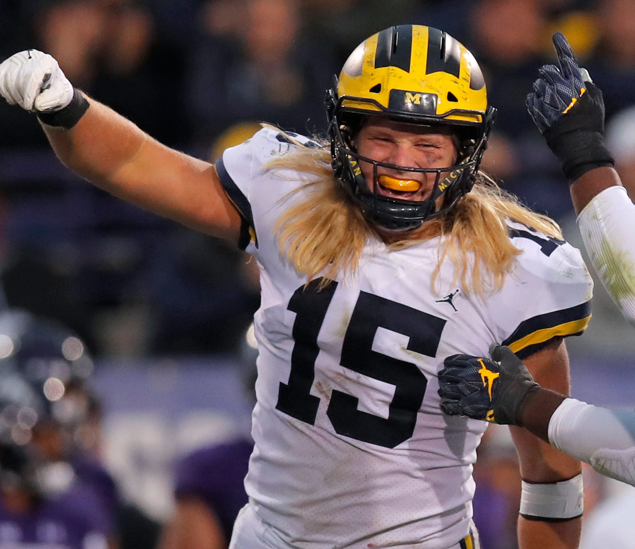 Michigan's Chase Winovich, left, Michael Dwumfour, center, and Devin Bush celebrate a sack against Northwestern on Saturday in Evanston, Ill.