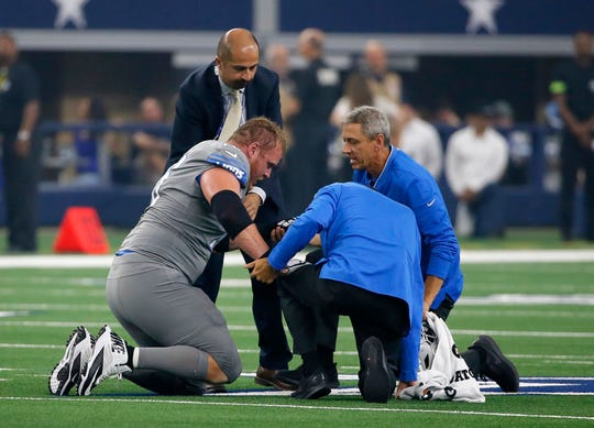 Lions offensive guard T.J. Lang, left, is attended to after an injury in the first half against the Dallas Cowboys in Arlington, Texas, Sunday, Sept. 30, 2018.