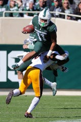 Michigan State running back Connor Heyward goes over a Central Michigan defensive back Devonni Reed during second half action Saturday, September 29, 2018 at Spartan Stadium in East Lansing, Mich.
