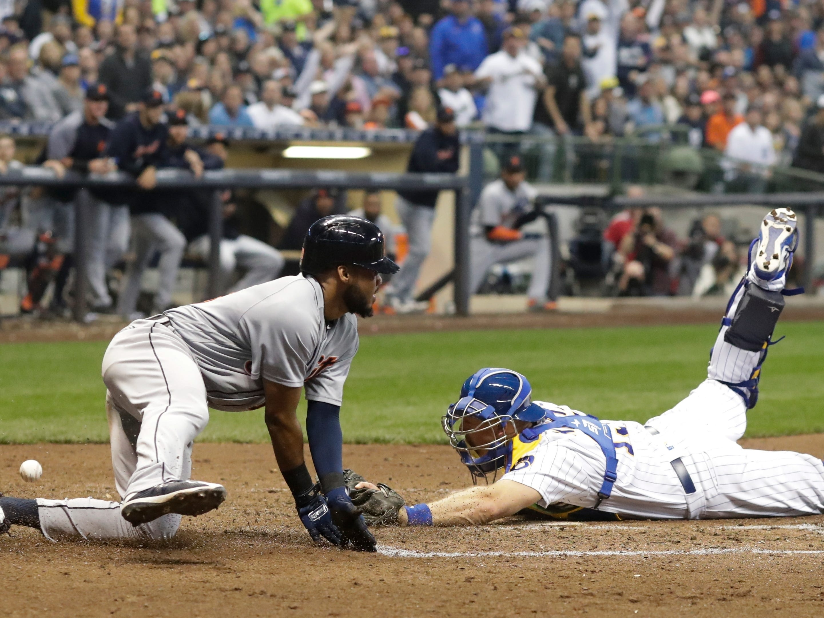 Detroit Tigers' Dawel Lugo scores safely past Milwaukee Brewers catcher Erik Kratz during the sixth inning Sept. 29, 2018, in Milwaukee. Lugo scored from third on a sacrifice fly.