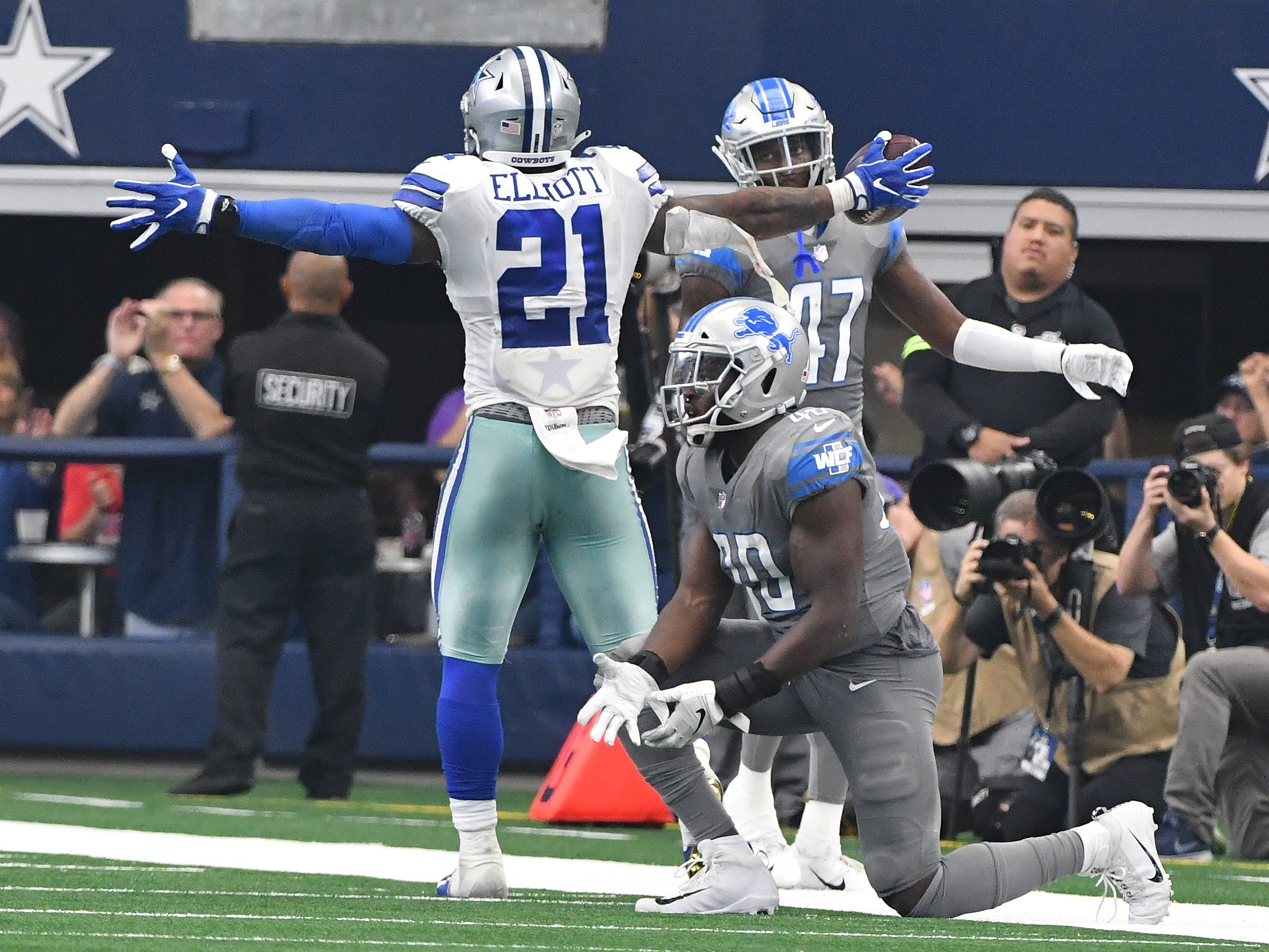 Cowboys running back Ezekiel Elliott celebrates as Lions linebacker Jarrad Davis slowly gets up, with teammate Tracy Walker, after Elliott makes a long first down reception over Davis to put Dallas within game winning field goal distance late in the fourth quarter.