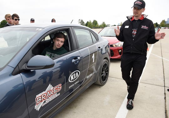 Brendon Short, 35,  Pro Driver Instructor teaches mirror and blind spot elimination (how to adjust your mirror) to Aidan Dyer, in car,16, of Northville and other teens during the class.  Young drivers participating in the B.R.A.K.E.S. Teen Active Driving School at Belle Isle Park. September 30, 2018. Detroit, MI.