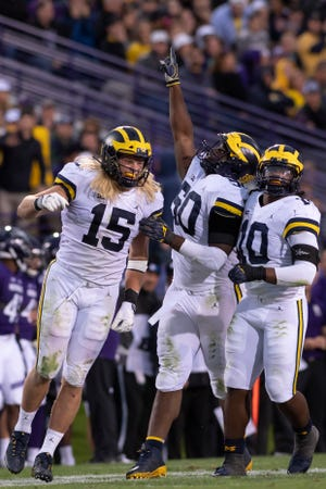 From left, Michigan's Chase Winovich, Michael Dwumfour and Devin Bush celebrate after a Dwumfour sack against Northwestern.
