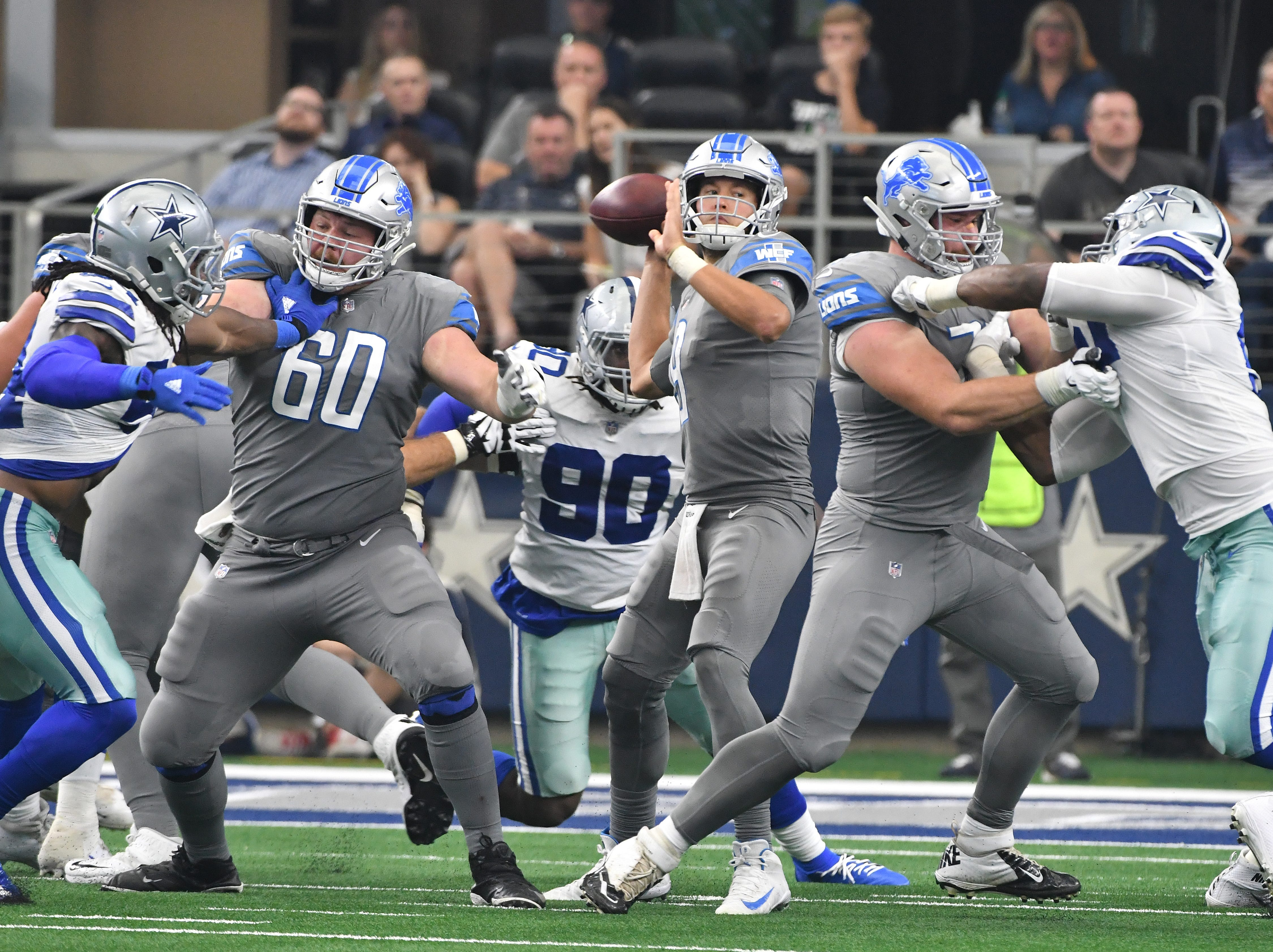 Lions quarterback Matthew Stafford looks for an open receiver as the offensive line works including Lions' Graham Glasgow and Frank Ragnow in the third quarter; unfortunately Stafford was sacked on this play.