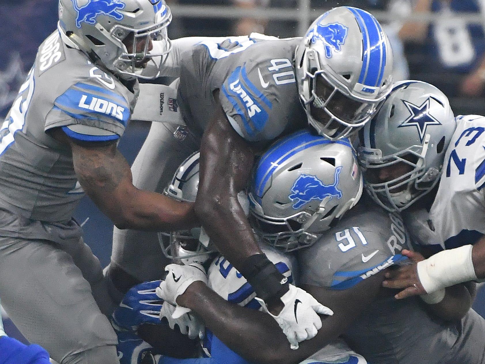 Lions' Quandre Diggs, Jarrad Davis and A'Shawn Robinson bring down Cowboys running back Ezekiel Elliott in the first quarter.