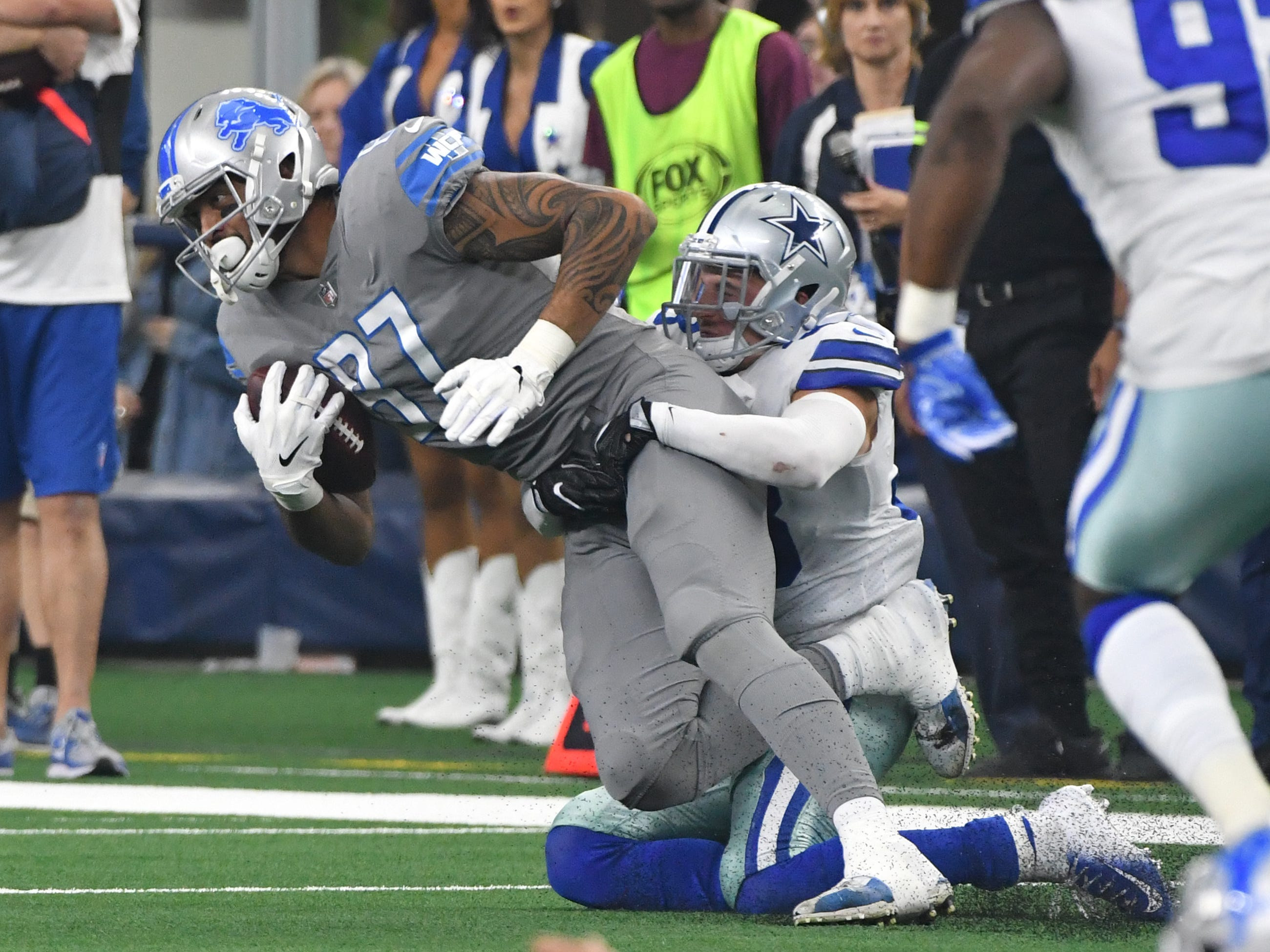 Lions tight end Levine Toilolo hangs onto a reception in front of Cowboys' Jeff Heath in the third quarter.
