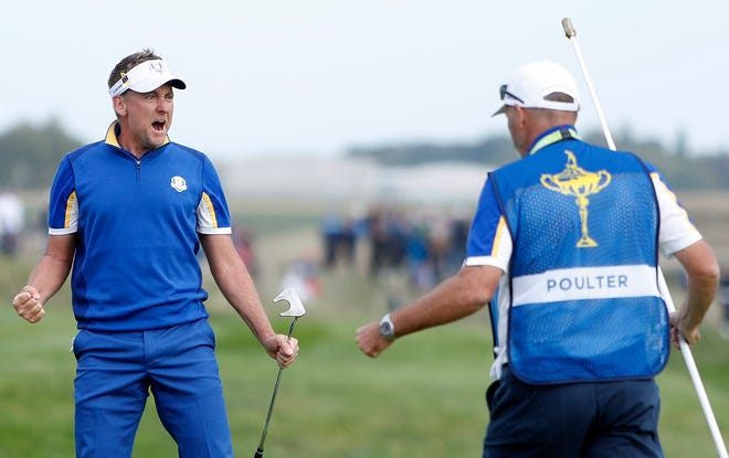 Europe's Ian Poulter celebrates after winning the 14th hole during a singles match on Sunday.