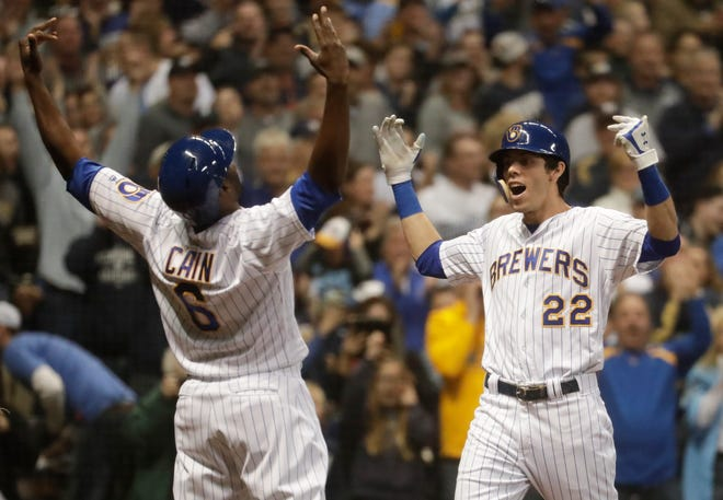 Milwaukee Brewers' Christian Yelich celebrates his two-run home run with Lorenzo Cain during the third inning on Saturday.