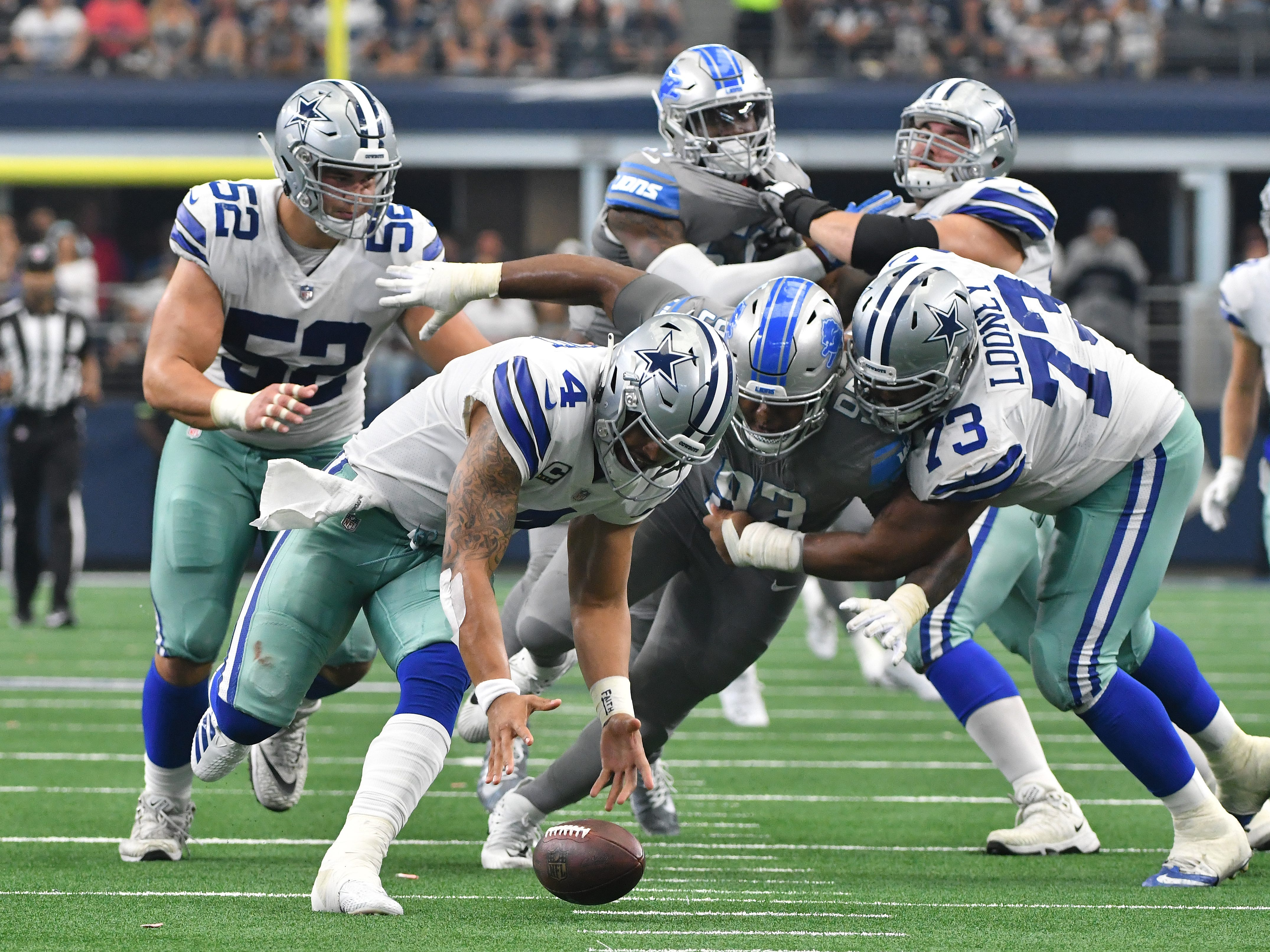 Cowboys quarterback Das Prescott's finds the football and begins to chase it down as teammate Joe Looney holds back Lions' Da'Shawn Hand who forced the fumble late in the fourth quarter.