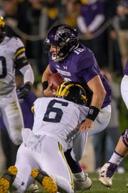Michigan linebacker Josh Uche sacks Northwestern quarterback Clayton Thorson to seal the win for the Wolverines on the last play of the game Saturday in Evanson, Ill.