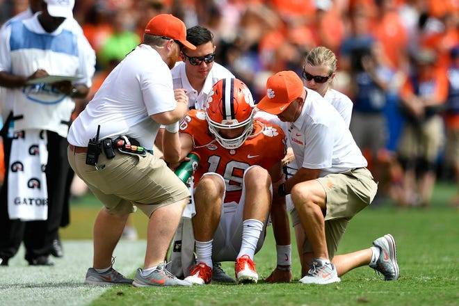 Clemson quarterback Trevor Lawrence is helped from the field after taking a hard hit during Saturday's game against Syracuse.