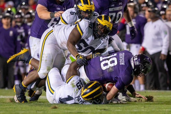 Northwestern quarterback Clayton Thorson is sacked by (from top) Michigan linebacker Josh Uche, defensive lineman Michael Dwumfour, and defensive lineman Kwity Paye in the fourth quarter Saturday in Evanston, Ill.