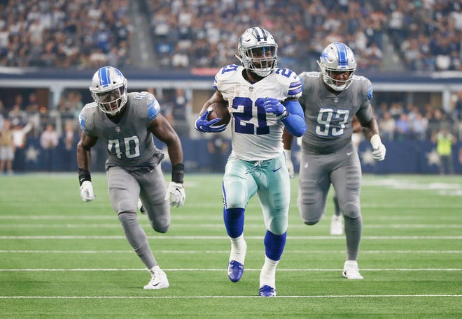 Dallas Cowboys running back Ezekiel Elliott carries the ball as Detroit Lions linebacker Jarrad Davis (40) and defensive end Da'Shawn Hand (93) give chase in the first half.
