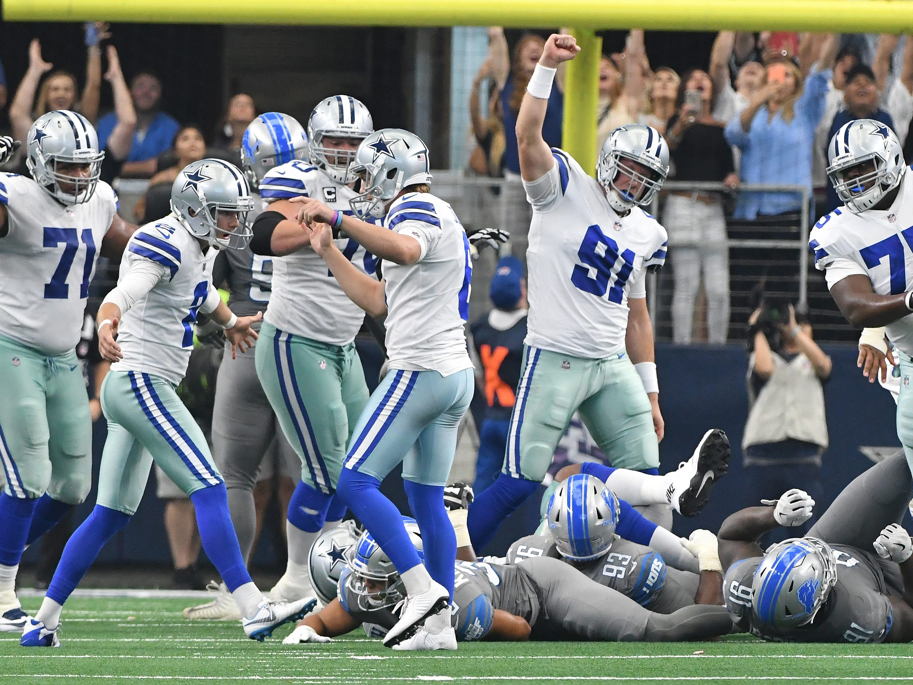 Cowboys players begin to celebrate with kicker Brett Maher after he splits the uprights with a last second field goal to win the game at the end of the fourth quarter.