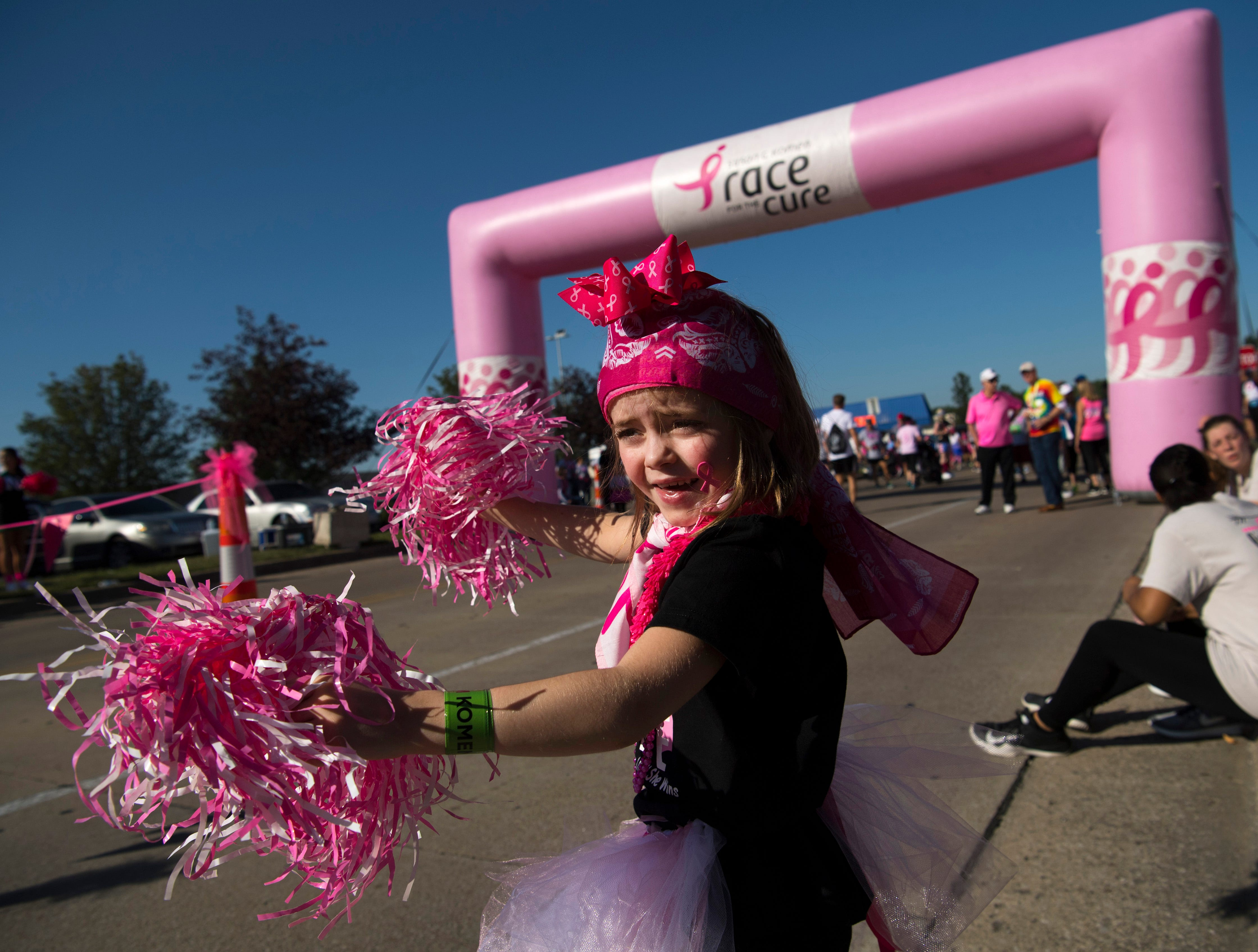 Lyric O'Rear, 6, of Madisonville, Ky., cheers finishers at the 2018 Susan G. Komen Race for the Cure at Eastland Mall Sunday morning. She was waiting for her grandmother, Jennifer Stone, a breast cancer survivor, to cross the finish line.