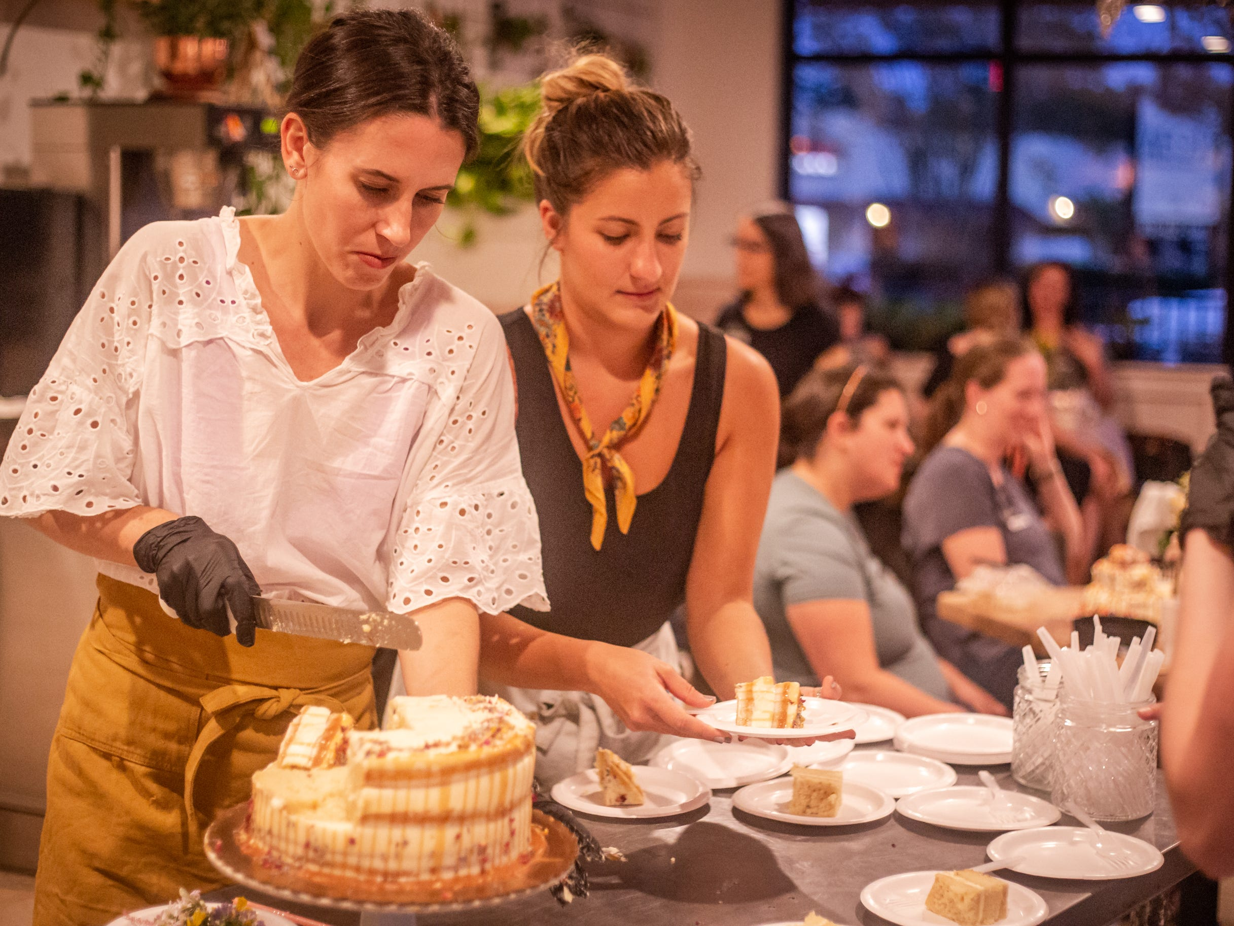 Lauren Poulos (left), SoDough baker and manager, cuts into SoDough's first birthday cake. The cake was assembled and decorated as part of the first class of the Autumn baking series held on Thursday, September 28, 2018 at SoDough in Tallahassee, FL.