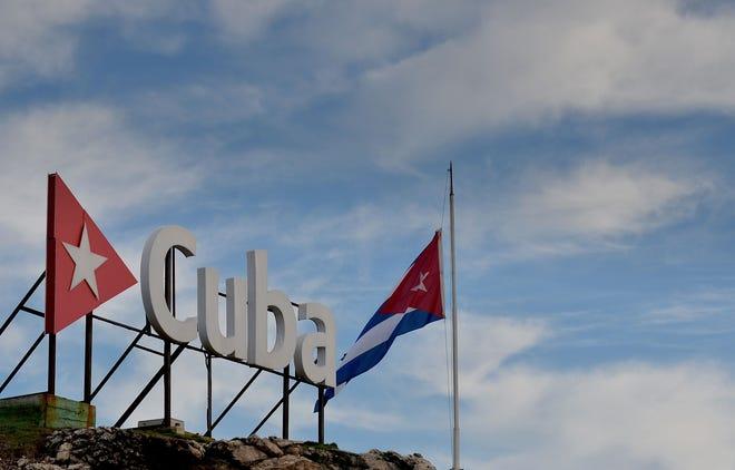 The Cuban national flag flying at half-mast.