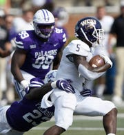 Furman inside linebacker Elijah McKoy (23) stops Western Carolina's Connell Young (5).