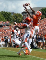 Clemson wide receiver Tee Higgins (5) reaches up for a ball he nearly catches next to Syracuse defensive back Trill Williams(22) during the third quarter in Memorial Stadium on Saturday, September 29, 2018.