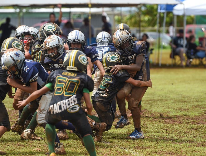 The Guam Packers' Jose Castro hits the Southern Cowboys' Darius Rockmore (2) during a Guam National Youth Football Federation Metgot Division game in Talofofo Sept. 30. The Packers won, 19-6.