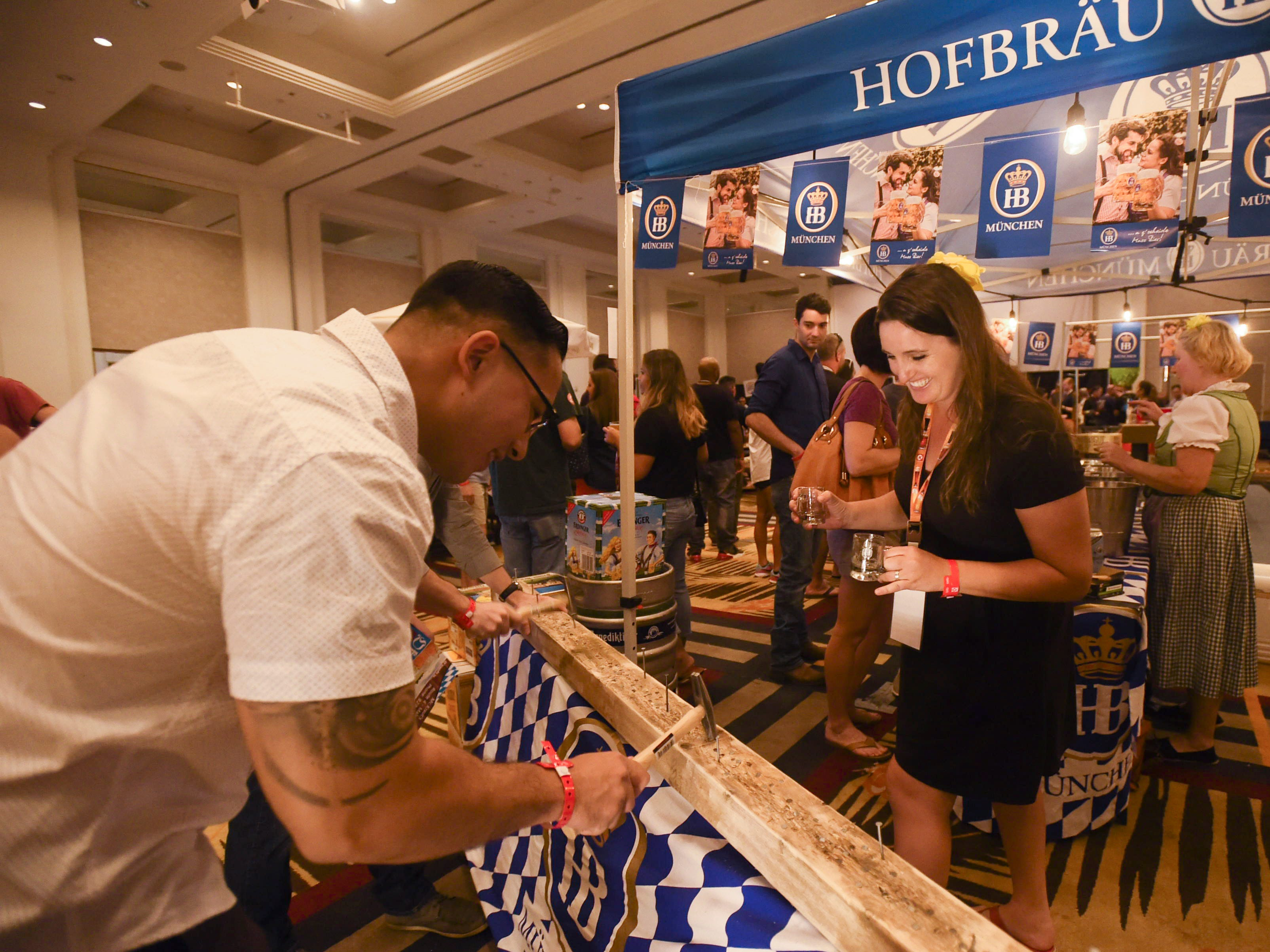Event goers try a game of Hammerschlagen at the Hofbräu München beer booth during the Circle K Craft Beer Festival in the Sheraton Laguna Guam Resort, Sept. 29, 2018.
