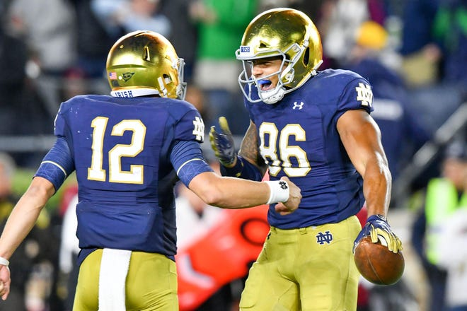 Notre Dame Fighting Irish tight end Alize Mack (86) celebrates with quarterback Ian Book (12) after a touchdown in the fourth quarter against the Stanford Cardinal at Notre Dame Stadium.