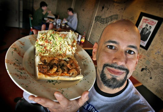 Papa Roux owner Art Bouvier, holds the house favorite shrimp po' boy sandwich on French bread. The Cajun restaurant in Indianapolis is scheduled to close for good Oct. 13, 2018.